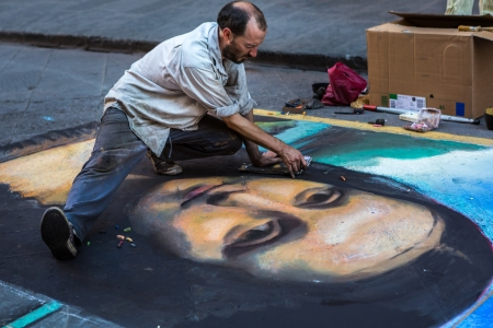 FLORENCE, ITALY - JULY 24  A street artist draws Mona Lisa, the famous Leonardo da Vinci painting, on asphalt on July 24, 2013 in Florence, Italy