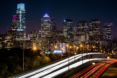 Philadelphia skyline by night  the rush hour traffic leaves trails of light on Schuylkill expressway Stock Photo - 23459959