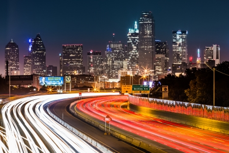 Dallas skyline by night  The rush hour traffic leaves light trails on I-30  Tom Landry  freeway