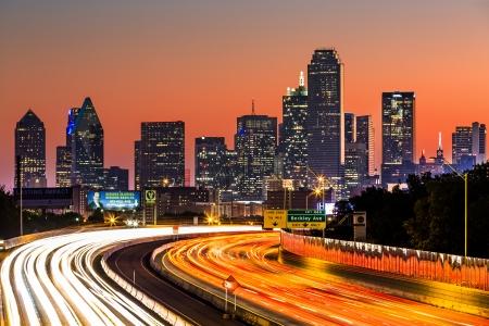 Dallas skyline at sunrise  The rush hour traffic leaves light trails on I-30  Tom Landry  freeway