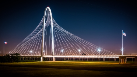 steel arch bridge:  Margaret Hunt Hill bridge by night in Dallas, USA  Margaret Hunt Hill Bridge is a Santiago Calatrava-designed bridge built over the Trinity River