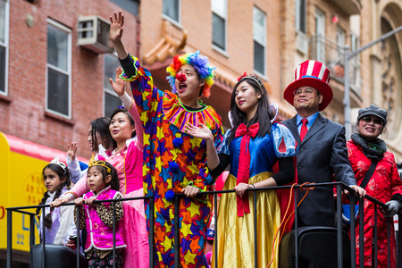 next year: Young man dressed in a clown costume salutes the crowd at the Lunar New Year Festival in Chinatown  Next to him parade young girls dressed as princesses