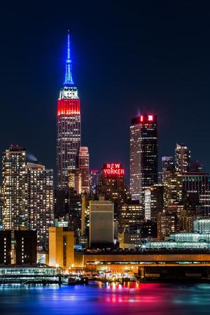 エンパイア ステート ビルディングの象徴的な高層ビルの上部を表示アメリカ国旗の色、青白赤い勲章、大統領の日の夜 報道画像