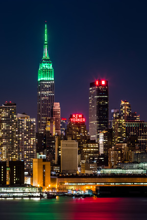 Empire State Building by night  The top of the iconic skyscraper is lit in green in honor of Saint Patrick Day  photo