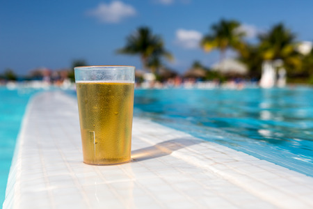 Glass of beer standing on the swimming pool ledge in an tropical resort photo