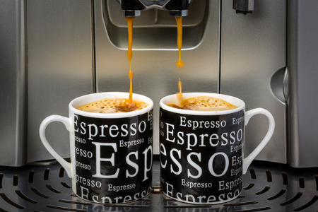 espresso machine: Two espresso cups filled by an automatic espresso machine Stock Photo