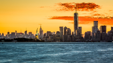 wtc: Sunrise over the Manhattan island with the Statue of Liberty facing Freedom Tower Stock Photo