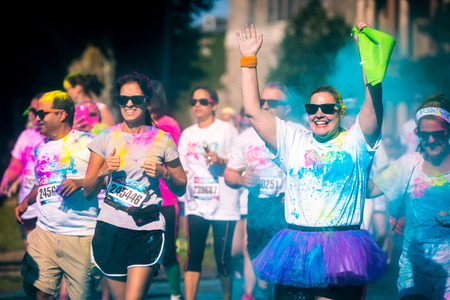 Happy woman runs the 5k Color Vibe race in Morristown, New Jersey  Color Vibe is a fun un-timed event with no winners or prizes where runners are showered with colored powder along the run