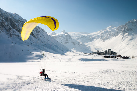 adventure aeronautical: Paraglider landing on skis in Tignes, a ski resort in the french Alps