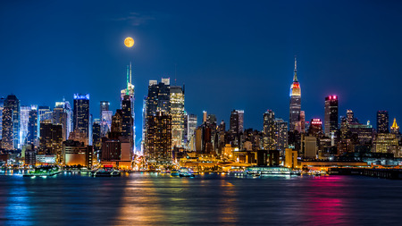 Super Moon above New York skyline  The top of the Empire State Building is illuminated with the colors of the German and Argentinian flags in honor of the Soccer World Cup final