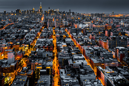roof: Aerial view of New York City at night with illuminated avenues converging towards midtown.