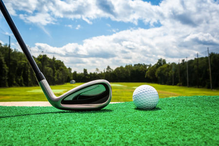 Close-up of a golf ball and a golf iron on a driving range photo