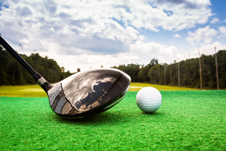 Close-up of a golf ball and a golf wood on a driving range photo