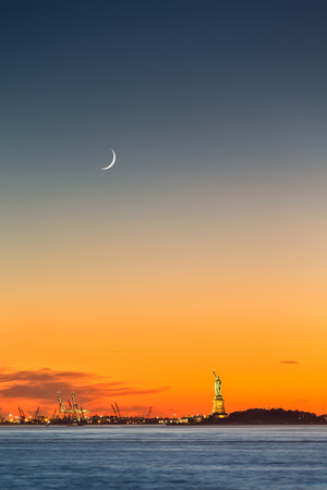 Statue of Liberty under a rising new moon at sunset