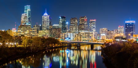 philadelphia: Philadelphia cityscape panorama by night. Schuylkill river reflects the colorful skyscrapers