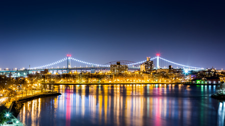 roosevelt: Queens cityscape by night framed by the illuminated RFK bridge (aka Triboro bridge) as viewed from Roosevelt island in New York.