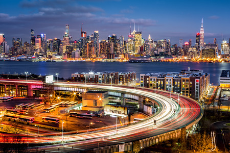 highway: Traffic and light trails on The Helix, a highway loop at the entrance in Lincoln Tunnel. The New York skyline shines in the background. Stock Photo