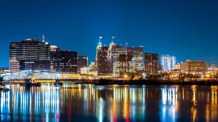 Newark, NJ paisaje urbano por la noche, vista desde el parque Riverbank. Jackson puente de la calle, iluminado, atraviesa el río Passaic