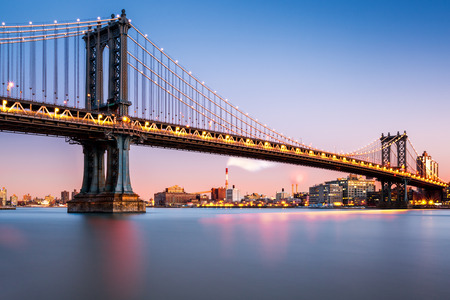 new york skyline: Manhattan Bridge illuminated at dusk (very long exposure for a perfectly smooth water) Stock Photo