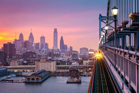 もやのかかった紫の夕日の下でフィラデルフィア。受信した列車は、ベン フランクリン橋を渡る。