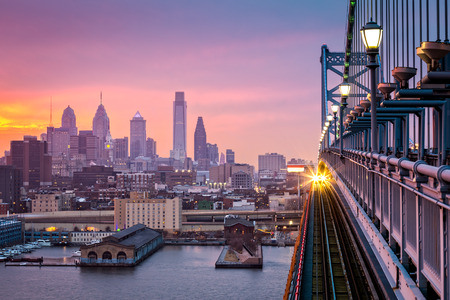 skyline: Philadelphia under a hazy purple sunset. An incoming train crosses Ben Franklin Bridge.