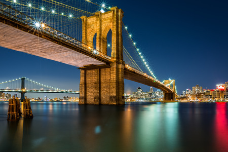 Illuminated Brooklyn Bridge by night as viewed from the Manhattan side