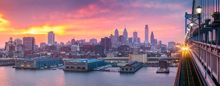 もやのかかった紫の夕日の下でフィラデルフィアのパノラマ。受信した列車は、ベン フランクリン橋を渡る。