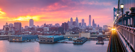 Philadelphia panorama under a hazy purple sunset. An incoming train crosses Ben Franklin Bridge.