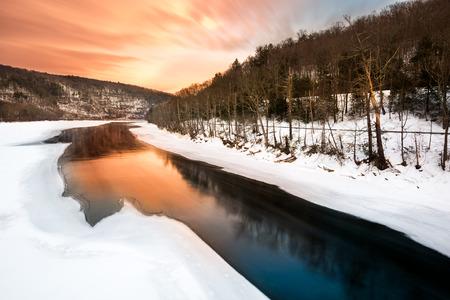 eddy: Sunset over a frozen Delaware river near Pond Eddy, New York Stock Photo