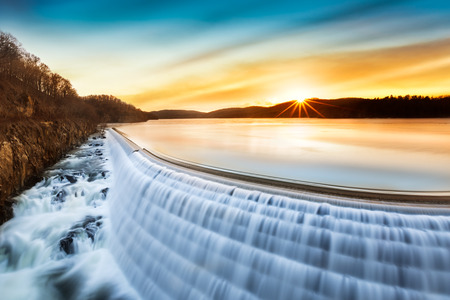 Sunrise over Croton Dam, NY and its stepped spillway waterfall. A very long exposure and the natural motion blur creates an artistic smooth and silky effect on the falling water. Stock Photo