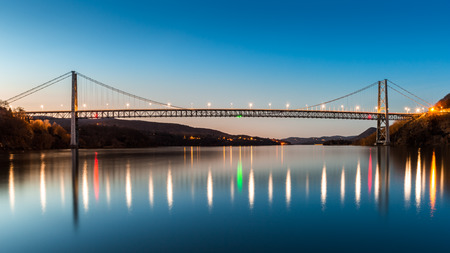 suspension bridge: Bear Mountain Bridge at dusk. Bear Mountain Bridge is a toll suspension bridge in New York State, carrying U.S. Highways 202 and 6 across the Hudson River Stock Photo