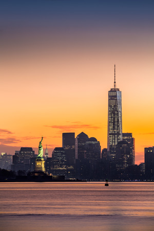 world trade center: Lower Manhattan with Freedom Tower and The Statue of Liberty at sunrise