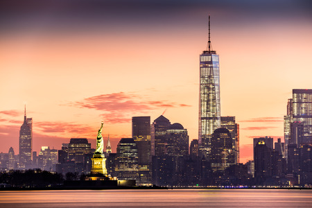 skyline city: Lower Manhattan with Freedom Tower and The Statue of Liberty at sunrise