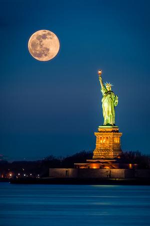 noche y luna: Estatua de la Libertad y un supermoon en ascenso en la ciudad de Nueva York