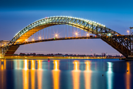 steel arch bridge: Bayonne Bridge at dusk. The Bayonne Bridge is the 5th longest steel arch bridge in the world spans the Kill Van Kull and connects Bayonne NJ with Staten Island NY Stock Photo