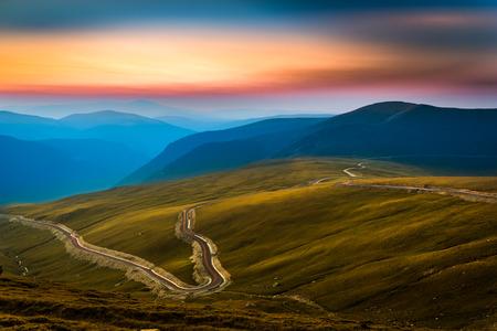 Transalpina 道路。Transalpina はルーマニアのカルパティア山脈を渡す最も高い道のひとつです。ヘイズの層は、夕暮れ山ピークをカバーします。