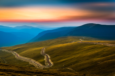 Transalpina road. Transalpina is one of the highest roads passing the Carpathians in Romania. Layers of haze cover the mountains peaks at sunset. Banque d'images