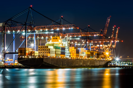export import: Cargo ship loaded in New York container terminal at night viewed from Elizabeth NJ across Elizabethport reach.