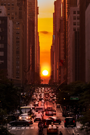 solstice: Manhattanhenge in New York City along the 42nd street. Manhattanhenge is an event during which the setting sun is aligned with the main street grid of Manhattan New York City