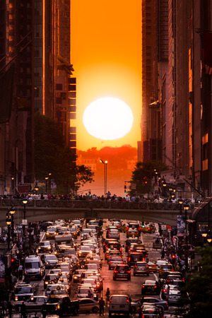 aligned: Manhattanhenge in New York City along the 42nd street. Manhattanhenge is an event during which the setting sun is aligned with the main street grid of Manhattan New York City