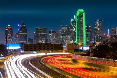 Dallas skyline bij nacht. Het spitsuur vertrekt licht paden op I30 Tom Landry snelweg.