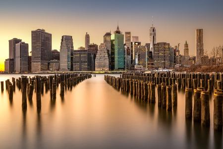 전경에있는 오래 된 브루클린 부두와 일몰 맨하탄 스카이 라인의 긴 노출