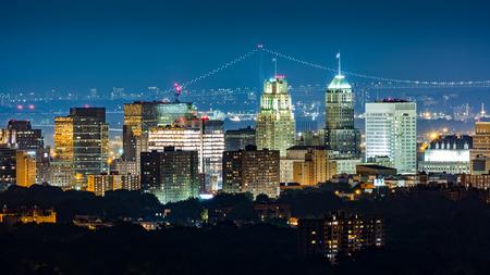 Newark, NJ, horizon op een wazige nacht met Verrazano Narrows Bridge op de achtergrond.