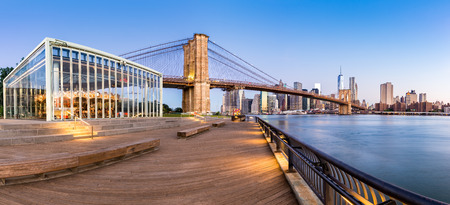 manhattan bridge: Brooklyn Bridge and the Lower Manhattan skyline panorama at sunrise as viewed from  Brooklyn Bridge Park riverbank, in New York City
