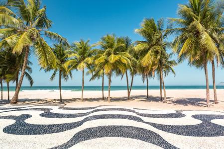 brazil beach: Palm trees and the iconic Copacabana beach mosaic sidewalk, in Rio de Janeiro, Brazil. Stock Photo