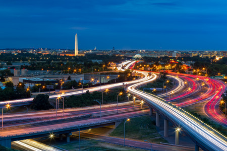 dc: Washington D.C. cityscape at dusk with rush hour traffic trails on I-395 highway. Washington Monument, illuminated, dominates the skyline.