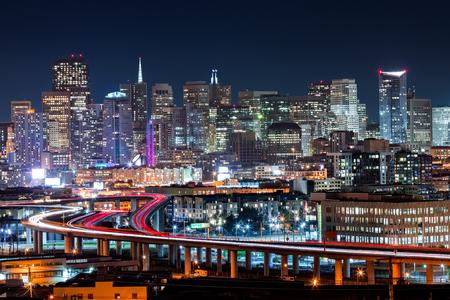 nacht: San Francisco Skyline mit Feierabendverkehr auf den gewundenen Straßen