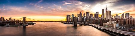 Brooklyn Bridge panorama at sunset. The iconic landmark spans between Brooklyn and the New York Financial District skyline, dominated by the Freedom Tower.
