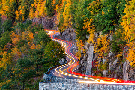 Traffic light trails on Hawk's Nest winding road route 97 in Upstate New York, on an autumn evening. 版權商用圖片 - 46591066