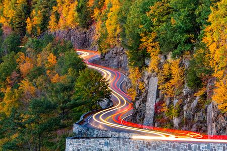 Verkeerslicht paden op Hawk's Nest bochtige weg route 97 in Upstate New York, op een herfstavond. Stockfoto